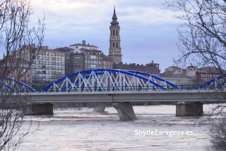 El nivel del agua a su  paso por el Puente de Hierro es muy alto. Aquí se ve la torre de La SEO de fondo.