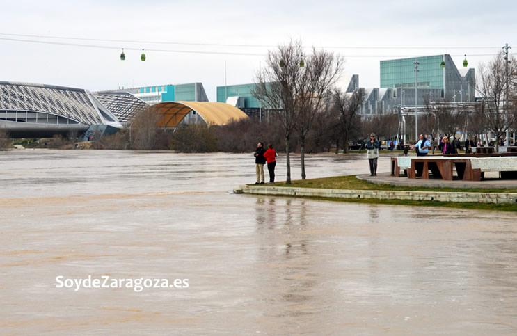 Muchas personas se acercan a hacer fotos a la crecida del río.