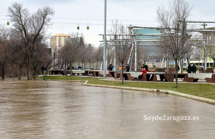 Los zaragozanos pasean por la zona observando la fuerza y altura del agua